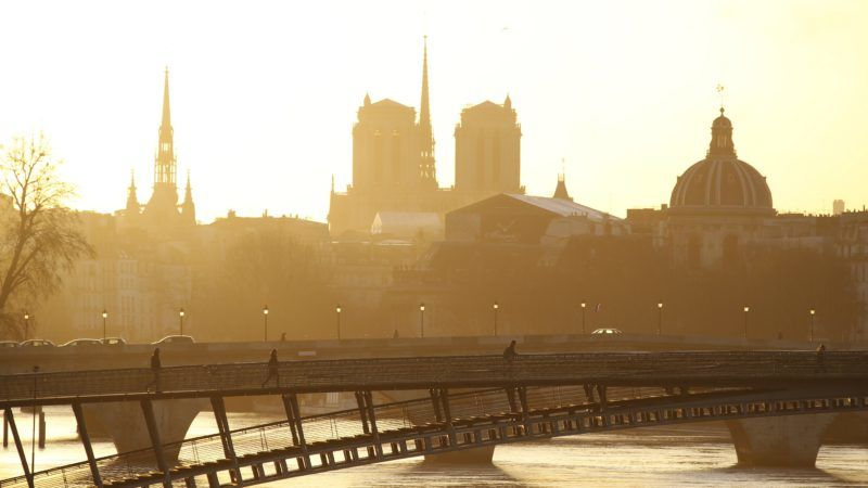 (FILES) In this file photo taken on February 12, 2014 people go to work while sunrise on river Seine, ile de la Cite, Sainte Chapelle, French Academy and the Notre Dame de Paris Cathedral. - A huge fire swept through the roof of the famed Notre-Dame Cathedral in central Paris on April 15, 2019, sending flames and huge clouds of grey smoke billowing into the sky. The flames and smoke plumed from the spire and roof of the gothic cathedral, visited by millions of people a year. (Photo by Ludovic MARIN / AFP)