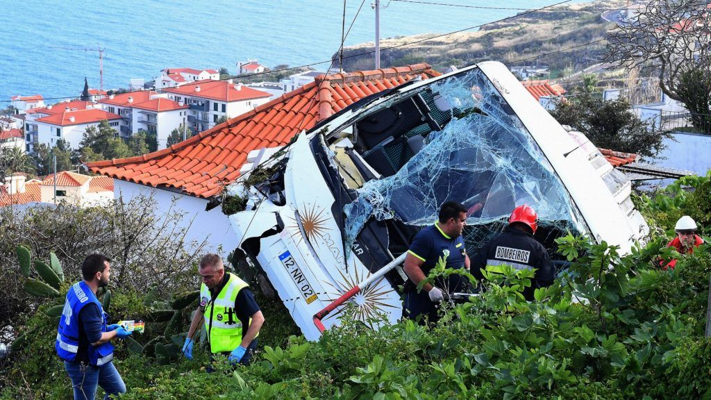 Firemen stand next to the wreckage of a tourist bus that crashed on April 17, 2019 in Caniço, on the Portuguese island of Madeira. - At least 28 people were killed when a tourist bus crashed on the Portuguese island of Madeira, the local mayor told local media. The regional protection service did not confirm the toll when questioned by AFP. (Photo by RUI SILVA / AFP)
