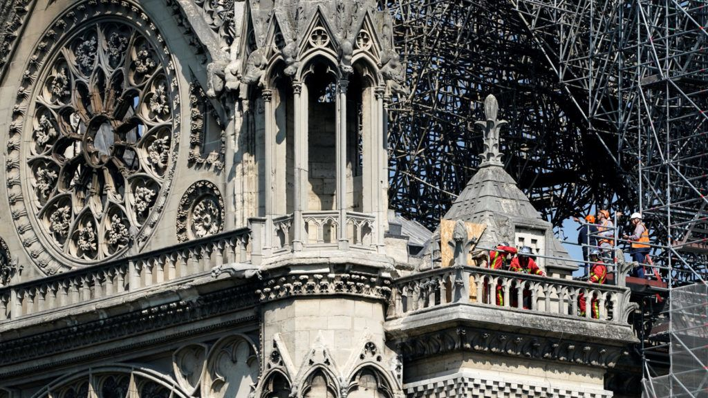 Firefighters and technicians work on a balcony of Notre-Dame de Paris Cathedral in Paris on April 19, 2019, four days after a fire devastated the cathedral. - Thousands of Parisians and tourists watched in horror from nearby streets on April 15 as flames engulfed the building and rescuers tried to save as much as they could of the cathedral's treasures built up over centuries. (Photo by Lionel BONAVENTURE / AFP)