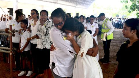 Two women mourn during a funeral service for bomb blast victims at St Sebastian's Church in Negombo on April 23, 2019, two days after a series of bomb attacks targeting churches and luxury hotels in Sri Lanka. - Sri Lanka began a day of national mourning on April 23 with three minutes of silence to honour more than 300 people killed in suicide bomb blasts that have been blamed on a local Islamist group. (Photo by Jewel SAMAD / AFP)