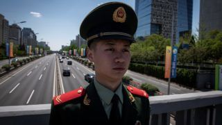 A paramilitary police officer secures an area next to banners (R) for the Belt and Road Forum displayed along a road in Beijing on April 25, 2019. (Photo by NICOLAS ASFOURI / AFP)