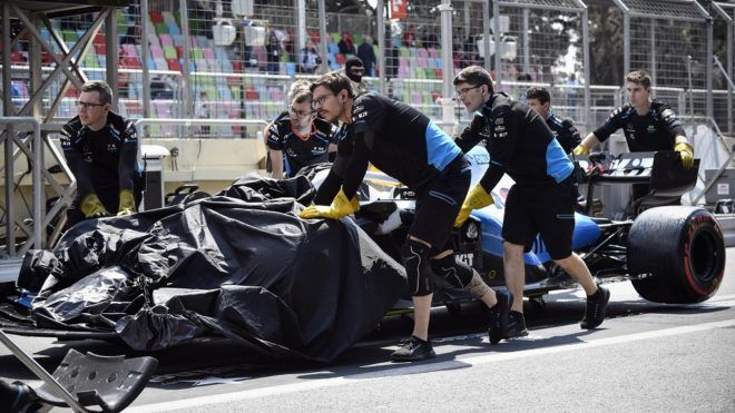 Technicians remove the damaged car of Williams' British driver George Russell during the first practice session ahead of the Formula One Azerbaijan Grand Prix in Baku on April 26, 2019. - George Russell running over a loose drain cover limited running in Free Practice 1 for the Azerbaijan Grand Prix to just 12 minutes as track repairs were effected. (Photo by Alexander NEMENOV / AFP)
