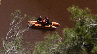 Cyprus forensic police officers search the Red Lake out of the village of Mitsero, southwest of the capital Nicosia on April 29, 2019. - Police recovered the remains of a fourth victim of a suspected serial killer in Cyprus where the search for bodies continued on April 29 after a string of grisly murders that have shocked the Mediterranean island. The woman's remains were found Sunday stuffed in a suitcase at the bottom of a toxic man-made lake next to a disused mine southwest of the capital Nicosia, police said. The suspect, a 35-year-old Greek Cypriot army officer, has allegedly confessed to killing five foreign women and two of their daughters in a crime spree that went undetected for nearly three years. (Photo by Iakovos Hatzistavrou / AFP)