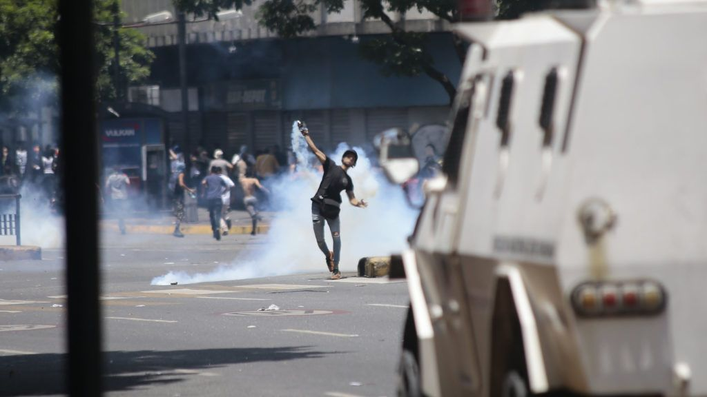 30 April 2019, Venezuela, Caracas: A demonstrator throws a tear-gas grenade against security forces in clashes in the capital. After the uprising of some soldiers against the government of Venezuelan President Maduro, demonstrators and government-loyal security forces in the capital of Caracas have fought hard. Photo: Rafael Hernandez/dpa