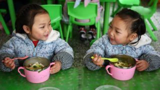 (190311) -- BEIJING, March 11, 2019 (Xinhua) -- Huang Xingqi (L) and her twin sister Huang Xingyi have free lunch at a kindergarten in Yuping Dong Autonomous County of Tongren, southwest China's Guizhou Province, Feb. 28, 2019. (Xinhua/Yang Wenbin)