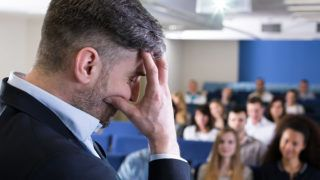 Close-up of a young academic teacher in a lecture room filled with students, hiding his face in his hand in a frustrated pose