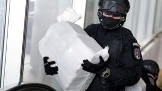 Bukarest, 2019. március 26. Különleges rendõri alakulat tagja viszi az általuk lefoglalt, kábítószert tartalmazó csaomagokat a szervezett bûnözés és terrorizmus elleni ügyészség (DIICOT) bukaresti székhelyén rendezett sajtótájékoztatón 2019. március 26-án. A tájékoztatón az utóbbi évek legnagyobb kábítószerfogásáról, csaknem egy tonna kokain lefoglalásáról számoltak be a román hatóságok. A drogot egy felborult bárka körül találták meg március 22-én a Fekete-tenger partján, a Duna-delta egy elhagyott térségében, a Szent-György ágnál. Az elõzetes vegyészszakértõi vélemény szerint a lefoglalt anyag 90 százalékos tisztaságú kokain, amelynek feketepiaci értékét a DIICOT fõügyésze 300 millió euróra (mintegy 95 milliárd forint) becsülte. MTI/EPA/Robert Ghement