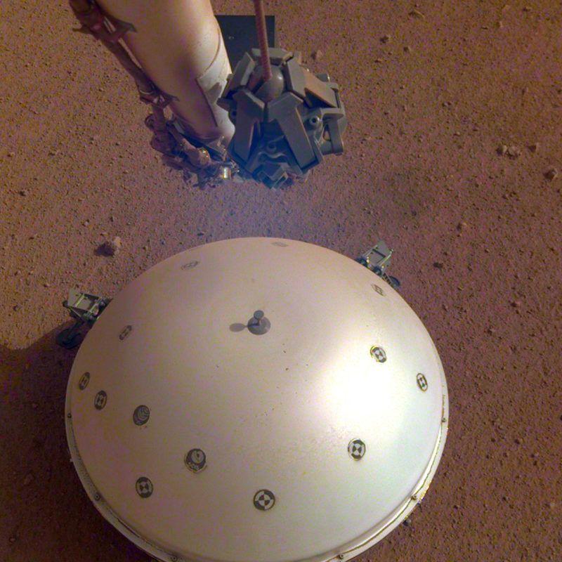 Világûr, 2019. április 24.Az amerikai Országos Repülésügyi és Ûrkutatási Hivatal, a NASA által 2019. április 23-án közreadott kép a NASA InSight nevû Mars-szondájának hõpajzzsal védett szeizmométerérõl. A francia ûrkutatási ügynökség, a Cnes közleménye szerint április 6-án gyenge, de világosan észlelhetõ rengést érzékelt a Marson az amerikai ûrszonda. A Mars belsejének kutatása céljából május 5-én útjára indított InSight robotgeológus ûrszonda mintegy 485 ezer kilométernyi út megtétele után 2018. november 26-án landolt a vörös bolygón.MTI/AP