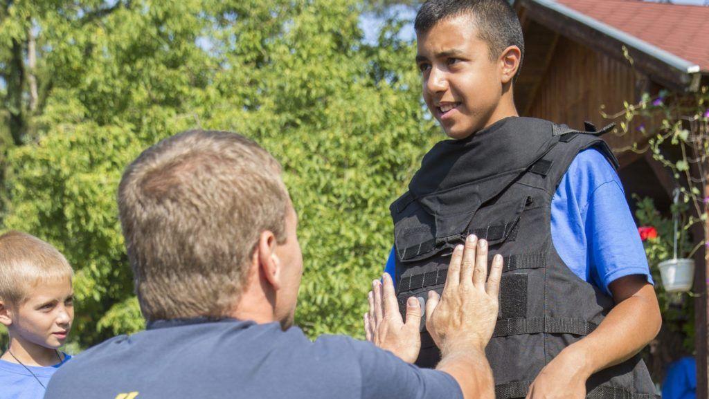 Szeghalom, 2015. augusztus 12. Egy fiú golyóálló mellényben a roma ifjúságvédelmi táborban, Szeghalom határában 2015. augusztus 12-én. MTI Fotó: Rosta Tibor