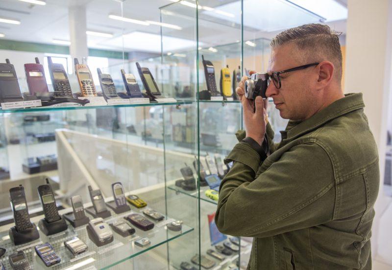 Szeged, 2019. április 15. Egy érdeklõdõ fotóz a mobiltelefonok történetét bemutató kiállításon a megnyitó napján a szegedi Szent-Györgyi Albert Agórában 2019. április 15-én. A táskaméretûtõl a miniatûrig több mint négyszázféle mobiltelefont ismerhetnek meg a látogatók a GSM - Generációk Saját Mobiljai címmel megnyílt idõszaki kiállításon. MTI/Rosta Tibor