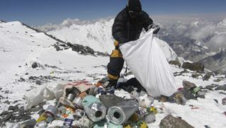 This picture taken on May 23, 2010 shows a Nepalese sherpa collecting garbage, left by climbers, at an altitude of 8,000 metres during the Everest clean-up expedition at Mount Everest. A group of 20 Nepalese climbers, including some top summiteers collected 1,800 kilograms of garbage in a high-risk expedition to clean up the world's highest peak. Led by seven-time summiteer Namgyal Sherpa, the team braved thin air and below freezing temperatures to clear around two tonnes of rubbish left behind by mountaineers, that included empty oxygen cylinders and corpses. Since 1953, there have been some 300 deaths on Everest. Many bodies have been brought down, but those above 8,000 metres have generally been left to the elements -- their bodies preserved by the freezing temperatures. The priority of the sherpas had been to clear rubbish just below the summit area, but coordinator Karki said large quantities of refuse was collected from 8,000 meters and below. AFP PHOTO/Namgyal SHERPA (Photo by NAMGYAL SHERPA / AFP)