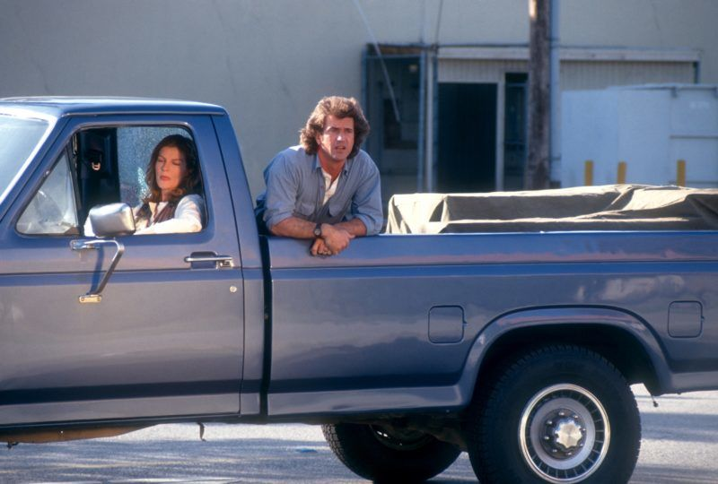 """LOS ANGELES, CA - 1992:  Actress Renee Russo drives a truck as actor Mel Gibson rides in the back during the filming of """"Lethal Weapon 3"""" circa 1992 in Los Angeles, California.  (Photo by Ron Davis/Getty Images)"""