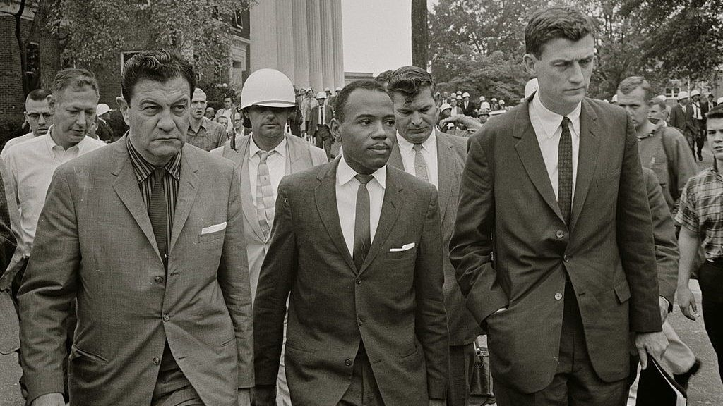 UNITED STATES -  1962:  James Meredith walking to class accompanied by U.S. marshals and lawyer John Doar (right).  (Photo by Buyenlarge/Getty Images)