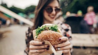 tasty burger. stylish hipster woman holding juicy hamburger in hands close up. boho girl with hamburger at street food festival. summertime. summer vacation picnic. space for text