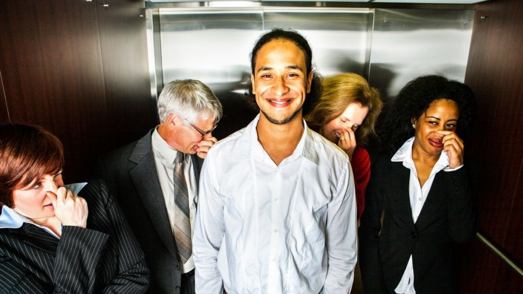 A young man smiles in embarrassment (or pride) in an elevator while people hold their noses.