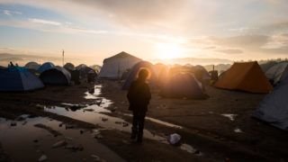 Idomeni, Greece - March 4, 2016: Refugee kid in front of hundreds of tents, during sunrise in Idomeni refugee camp. Borders with Former Yugoslavic Republic of Macedonia. 12000 immigrants are in a wait at the border between Greece and FYROM waiting for the right time to continue their journey from unguarded passages. The borders have been closed and guarded against immigrants passing.