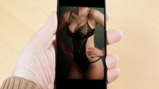 male hand holding smart phone showing sexy photo of female body in lingerie