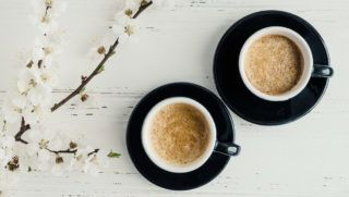 Two cups of coffee Espresso and cherry blossom on shabby chic wooden table. Breakfast on Womens, Valentines or Mothers day. Spring morning concept. Top view.