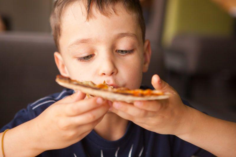 Child  having fun eating pizza  bar restaurant