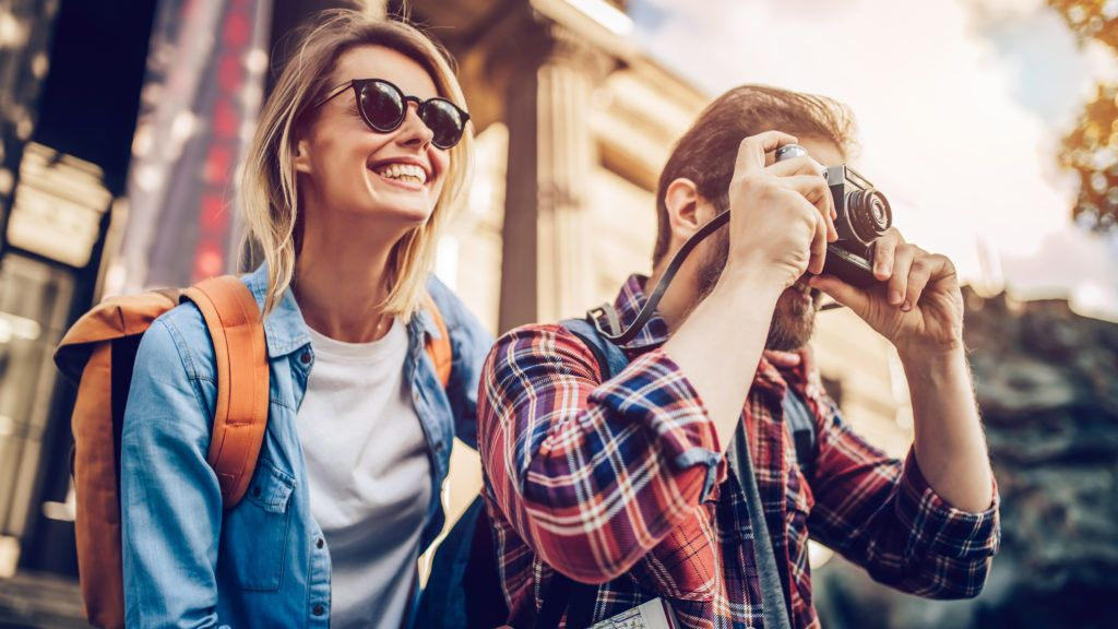 Couple of tourists is exploring new city together. Smiling and making photo on a retro camera.