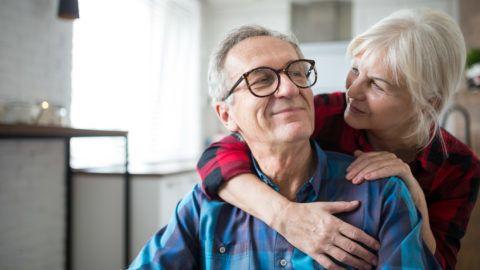 Portrait of happy senior woman embracing her husband