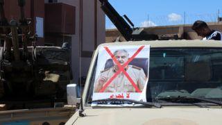 """Tripoli, 2019. április 8. Halifa Haftar tábornok áthúzott portréja egy miszrátából érkezõ katonai terepjárón, mielõtt a líbiai fõváros, Tripoli felé indulnak 2019. április 8-án. Az ország keleti részét uraló Halifa Haftar tábornok erõi április 4-én indultak Tripoli ellen, ahol a nemzetközi segítséggel felállított egységkormány mûködik. Haftar közölte, hogy megtisztítja az országot a """"terroristáktól és zsoldosoktól"""". Az Európai Unió április 8-án támadásai leállítására szólította fel Haftar tábornokot. Az összecsapásokban eddig legkevesebb 25 ember vesztette életét. MTI/EPA"""
