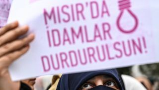 """A woman holds a sign reading """"Stop executions in Egypt"""" in front of the Egyptian consulate in Istanbul on march 2, 2019 during a demonstration against death penalties in Egypt after the recent execution of nine men. - Egypt on February 20 hanged nine men for the 2015 assassination of prosecutor general Hisham Barakat following jihadist calls for attacks on the judiciary to avenge the government's crackdown on Islamists. Turkish President sharply criticised his Egyptian counterpart and called for the release of Muslim Brotherhood prisoners in Egypt. (Photo by Ozan KOSE / AFP)"""