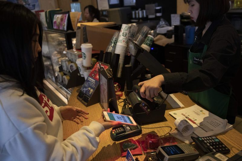 """A woman uses an Apple Iphone to pay for her coffee at a Starbucks shop in Beijing on January 3, 2019. - Apple cut its revenue outlook for the latest quarter on January 3, citing steeper-than-expected """"economic deceleration"""" in China and emerging markets. (Photo by Nicolas ASFOURI / AFP)"""