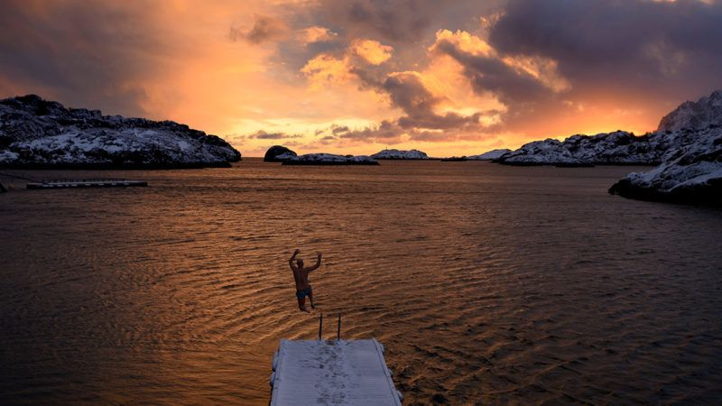 A man jumps in the cold water (3C), on February 19, 2019, in Kabelvag, in Lofoten island, Northern norway. (Photo by Olivier MORIN / AFP)