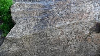 This picture taken on May 7, 2019 shows inscriptions composing indecipherable words on a rock in the Brittany village of Plougastel-Daoulas. - The city launched a national call with a 2000 euros reward to anyone able to solve the mystery of those inscriptions propably made during the 18th century. (Photo by Fred TANNEAU / AFP)