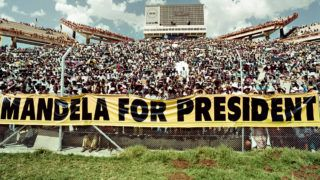 A crowd of estimated 40.000 African National Congress (ANC) supporters listen to the address of ANC President Nelson Mandela during a mass rally in Mmabatho 15 March 1994 prior to the 27 April general election. South Africans will vote 27 April 1994 in the country's first democratic and multiracial general elections. Mmabatho Stadium is a multi-purpose stadium in Mafikeng, South Africa. It is currently used mostly for football matches. The stadium holds 59,000 people and was designed and built in 1981 by a Russian construction firm. The South African general election of 1994 was an election held in South Africa to mark the end of apartheid, therefore also the first held with universal adult suffrage.  AFP PHOTO WALTER DHLADHLA (Photo by WALTER DHLADHLA / AFP)