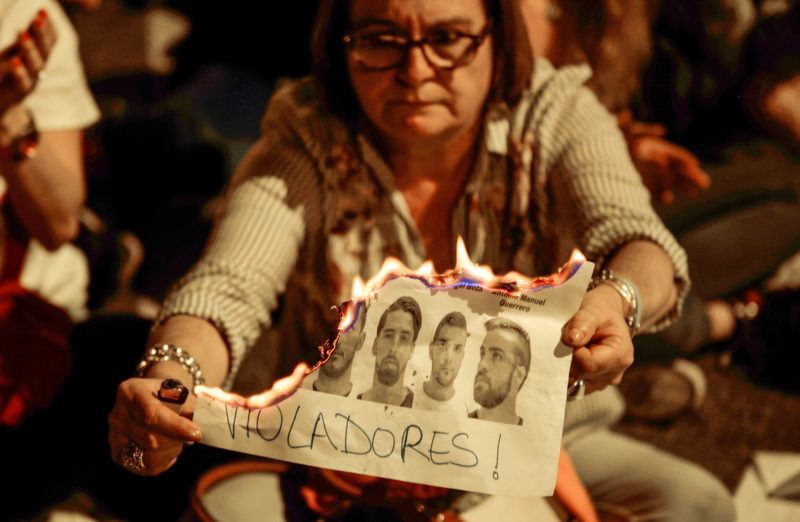 """A woman burning a photographs of the five men known as """"La Manada"""" during a protest in Madrid on 26 April, 2018.  The High Court of Navarra has given a sentence of 9 years in prison to five men for 'continued sexual abuse' instead of 'rape', which they would have recieved around 22 years in prison. The gang assaulted an 18-year-old woman in Pamplona, during the San Fermin Festival in 2016. Feminists and women's rights groups have called for demonstrations across Spain. (Photo by Juan Carlos Lucas/NurPhoto)"""