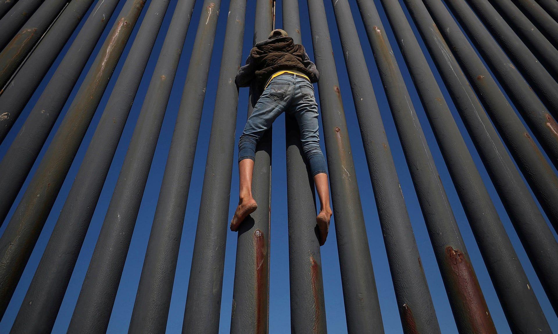 A menekŸlt karav‡n egyik kšzŽpamerik‡b—l intœlt tagja pr—b‡lja meg ‡tm‡szni a ker'tŽst az amerikai mexik—i hat‡ron. Fot—: Hannah McKay / Reuters / thebppa