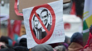 A protester holds a sign depicting Austria's Chancellor Sebastian Kurz (L) and Austrian Vice Chancellor Heinz-Christian Strache during a rally a year after the forming of a government by the conservative Oevp - FPOe parties on December 15, 2018 in Vienna. (Photo by ALEX HALADA / AFP)