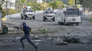 Anti-government protesters clash with security forces during the commemoration of May Day on May 1, 2019 after a day of violent clashes on the streets of the capital spurred by Venezuela's opposition leader Juan Guaido's call on the military to rise up against President Nicolas Maduro. - Guaido called for a massive May Day protest to increase the pressure on President Maduro. (Photo by Matias Delacroix / AFP)