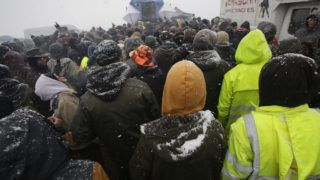 Participants of the Teknival techno music festival listen music as snow falls on May 4, 2019 in Feniers, central France. (Photo by PASCAL LACHENAUD / AFP)
