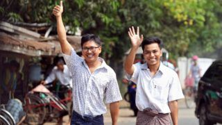 Reuters journalists Wa Lone (L) and Kyaw Soe Oo gesture as they walk to Insein prison gate after being freed in a presidential amnesty in Yangon on May 7, 2019. - Two Reuters journalists who had been jailed for their reporting on the Rohingya crisis in Myanmar walked out of prison on May 7, freed in a presidential amnesty after a global campaign for their release. (Photo by ANN WANG / POOL / AFP)