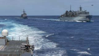 """This handout picture released by the US Navy on May 8, 2019 shows (L) the Ticonderoga-class cruiser USS Leyte Gulf (CG 55) pulling alongside (R) the fast combat support ship USNS Arctic (T-AOE 9) after the Arleigh Burke-class guided-missile destroyer USS Bainbridge (DDG 96) completes its replenishment-at-sea in the Mediterranean. - The US is deploying an amphibious assault ship and a Patriot missile battery to bolster an aircraft carrier and B-52 bombers already sent to the Gulf, ratcheting up pressure on Iran. The USS Arlington, which transports marines, amphibious vehicles, conventional landing craft and rotary aircraft, and the Patriot air defence system will join the Abraham Lincoln carrier group, the Pentagon announced on May 10. (Photo by MCSN Jason Waite / Navy Office of Information / AFP) / RESTRICTED TO EDITORIAL USE - MANDATORY CREDIT """"AFP PHOTO /US NAVY"""" - NO MARKETING NO ADVERTISING CAMPAIGNS - DISTRIBUTED AS A SERVICE TO CLIENTS"""