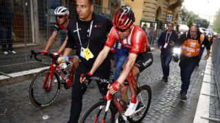 Team Sunweb rider Netherlands' Tom Dumoulin is escorted by a staff member after a crash in the stage four of the 102nd Giro d'Italia - Tour of Italy - cycle race, 235kms from Orbetello to Frascati on May 14, 2019. (Photo by Luk BENIES / AFP)