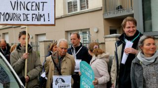 """A member of the support committee of French quadriplegic Vincent Lambert holds a placard reading """"Don't let Vincent starving to death"""" as he protests in front of the Sebastopol hospital in Reims, eastern France, on May 19, 2019. - The parents of a Frenchman kept alive in a vegetative state following a car accident in 2008 will on May 20, 2019 try to have the doctor caring for their son removed before he halts life-sustaining treatment the same day, their lawyers said. (Photo by FRANCOIS NASCIMBENI / AFP)"""