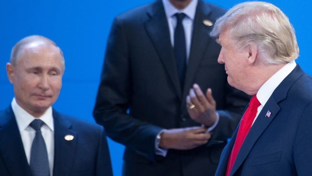 """30 November 2018, Argentina, Buenos Aires: Donald Trump (r), President of the United States, walks past Paul Kagame (M), President of Rwanda, and Vladimir Putin, President of Russia, at the G20 Summit Meeting Centre in Buenos Aires during the family photo. From 30.11.-1.12.2018 the G20 summit will take place in Buenos Aires. The """"Group of 20"""" unites the strongest industrial nations and emerging economies. Photo: Ralf Hirschberger/dpa"""