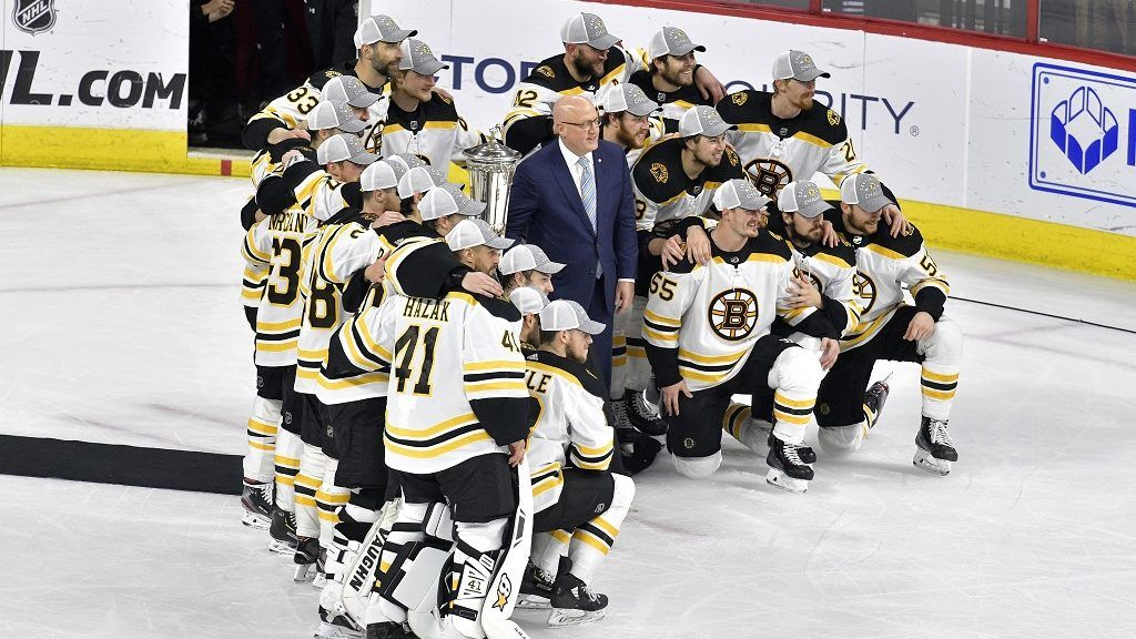 RALEIGH, NORTH CAROLINA - MAY 16: The Boston Bruins pose with the Deputy Commissioner Bill Daly and the Prince of Wales Trophy after defeating the Carolina Hurricanes in Game Four to win the Eastern Conference Finals during the 2019 NHL Stanley Cup Playoffs at PNC Arena on May 16, 2019 in Raleigh, North Carolina.   Grant Halverson/Getty Images/AFP