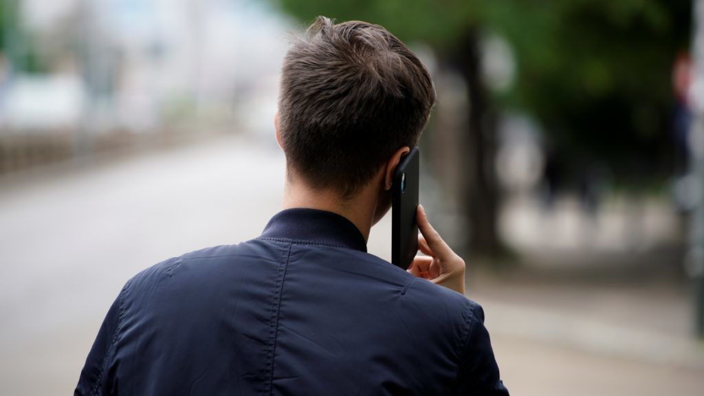 A young man walks while speaking on his mobile phone in Bucharest, Romania on May 1, 2019. (Photo by Jaap Arriens/NurPhoto)