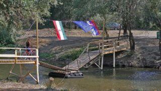 Drégelypalánk, 2007. augusztus 8. Egy kerékpáros halad át Drégelypalánk és a szlovákiai Ipolyhídvég (Ipelské Predmostie) között az Ipoly folyó két partján álló stég közé, csónakokra szerelt fahidon. Híd hiányában ez a kényszermegoldás teszi lehetővé a két település közötti gyalogos forgalmat. MTVA/Bizományosi: Gyukics Péter  *************************** Kedves Felhasználó! Az Ön által most kiválasztott fénykép nem képezi az MTI fotókiadásának, valamint az MTVA fotóarchívumának szerves részét. A kép tartalmáért és a szövegért a fotó készítője vállalja a felelősséget.