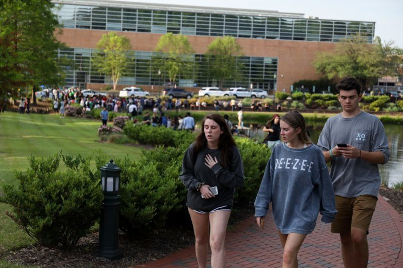 Students and faculty file out of buildings during a lockdown after a shooting on the campus of University of North Carolina Charlotte in University City, Charlotte, on April 30, 2019. - Six people were shot, two of them died on the University of North Carolina Charlotte campus. One person was taken into custody, according to police sources. (Photo by Logan Cyrus / AFP)