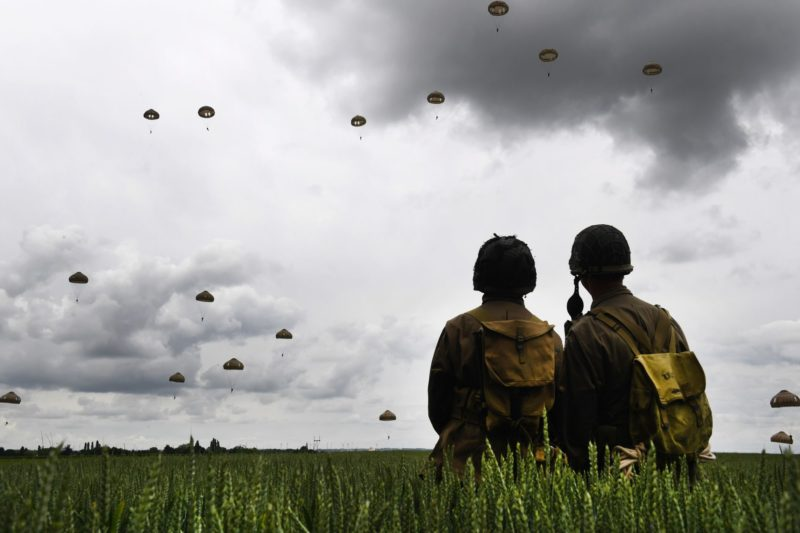 Men dressed as US GIs stand in a field as paratroopers from Britain's 16 Air Assault Brigade and France's 11th Parachute Brigade perform a jump over Sannerville, north-western France, on June 5, 2019, prior to D-Day commemorations marking the 75th anniversary of the World War II Allied landings in Normandy. (Photo by Fred TANNEAU / AFP)
