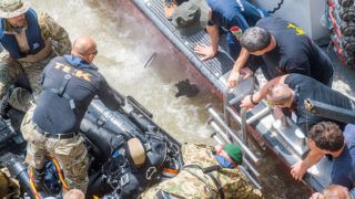 Budapest, 2019. május 31.A roncsfeltáró munkálatokat végző búvárok egyike nyújtja ki kezét a vízből az őt kihúzni készülő társai felé a hajóbalesetben elsüllyedt Hableány turistahajó közelében, a Margit hídnál 2019. május 31-én. A Hableány turistahajó és a Viking Sigyn szállodahajó május 29-én éjszaka ütközött össze a Margit híd közelében, majd a turistahajó felborult és elsüllyedt fedélzetén 33 dél-koreai turistával és a kéttagú magyar személyzettel. A balesetben heten meghaltak, hét embert kimentettek, 21-en eltűntek.MTI/Balogh Zoltán