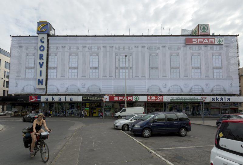 Budapest, 2018. június 18. Az épület eredeti homlokzatát mintázó háló fedi a felújítás alatt álló Corvin áruház köré felállított állványzatot a fõvárosi Blaha Lujza téren 2018. június 18-án. MTI Fotó: Mohai Balázs