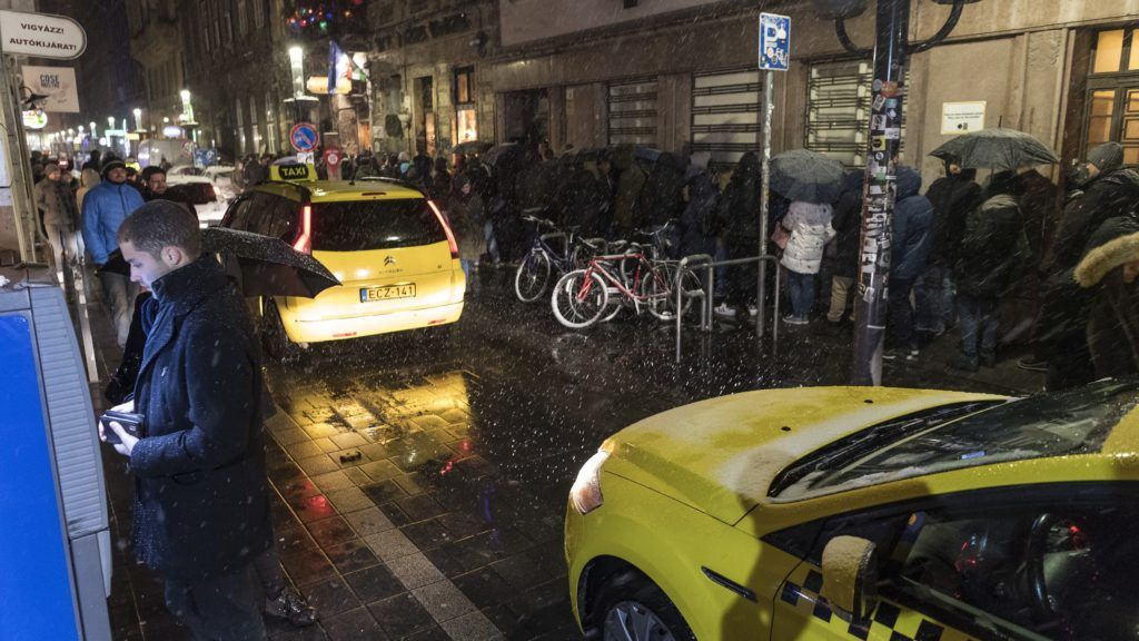 Budapest, 2018. február 18. Taxik haladnak el a bejutásra váró, sorban álló vendégek mellett a Szimpla Kert vendéglátóhely elõtt az erzsébetvárosi vigalmi negyedben a Kazinczy utcában 2018. február 18-ra virradó éjjel. Ezen a napon népszavazást tartanak arról, hogy a fõváros VII. kerületében, az úgynevezett bulinegyedben található vendéglátóhelyek éjfél és reggel 6 óra között nyitva tarthassanak-e. MTI Fotó: Szigetváry Zsolt