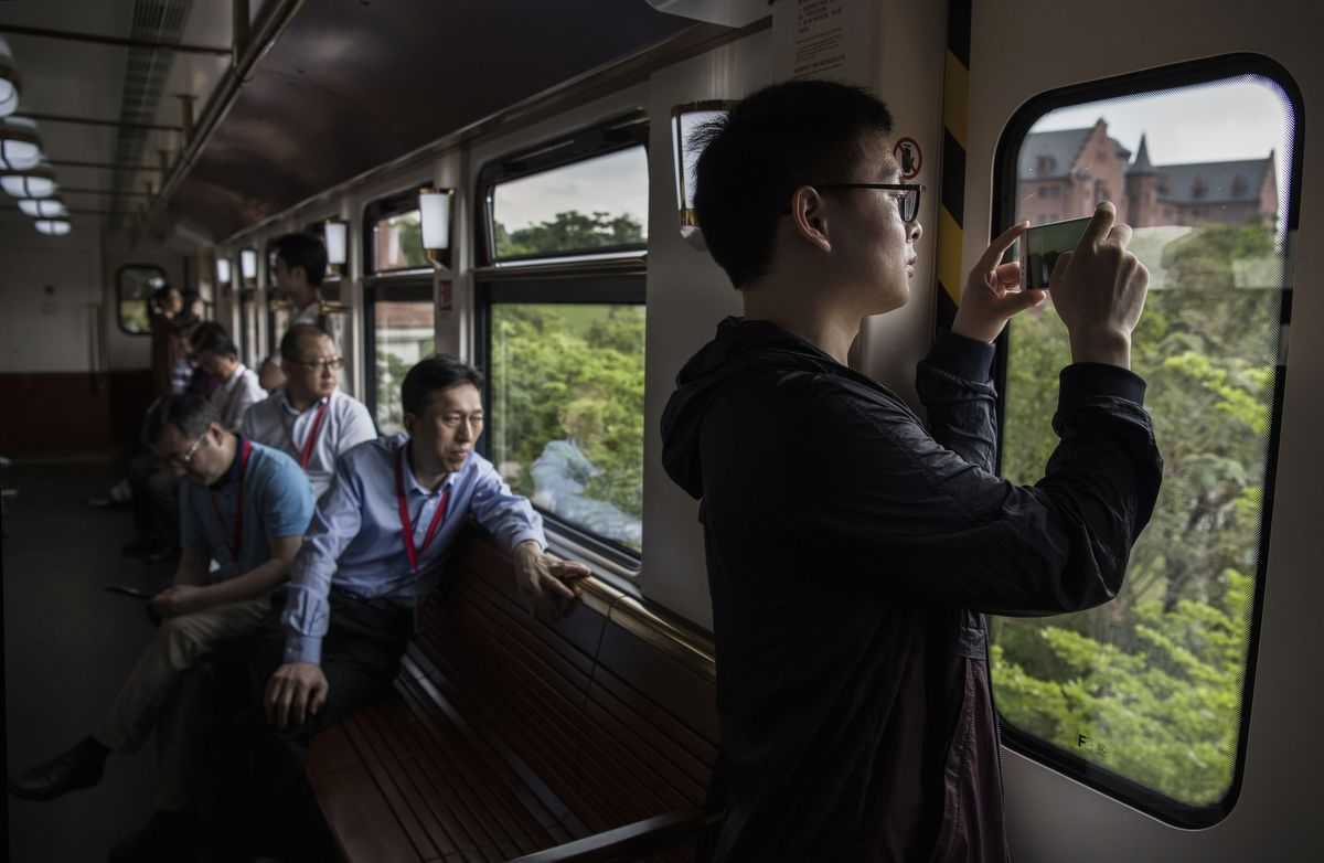 DONGGUAN, CHINA - APRIL 11: A man takes pictures out the window of a train used by Huawei workers, client, and other visitors at the company's new sprawling 'Ox Horn' Research and Development campus on April 11, 2019 in Dongguan, near Shenzhen, China. Huawei is Chinas most valuable technology brand, and sells more telecommunications equipment than any other company in the world, with annual revenue topping $100 billion U.S.  Headquartered in the southern city of Shenzhen, considered Chinas Silicon Valley, Huawei has more than 180,000 employees worldwide, with nearly half of them engaged in research and development. In 2018, the company overtook Apple Inc. as the second largest manufacturer of smartphones in the world behind Samsung Electronics, a milestone that has made Huawei a source of national pride in China.While commercially successful and a dominant player in 5G, or fifth-generation networking technology, Huawei has faced political headwinds and allegations that its equipment includes so-called backdoors that the U.S. government perceives as a national security. U.S. authorities are also seeking the extradition of Huaweis Chief Financial Officer, Meng Wanzhou, to stand trial in the U.S. on fraud charges. Meng is currently under house arrest in Canada, though Huawei maintains the U.S. case against her is purely political. Despite the U.S. campaign against the company, Huawei is determined to lead the global charge toward adopting 5G wireless networks.  It has hired experts from foreign rivals, and invested heavily in R&D to patent key technologies to boost Chinese influence.(Photo by Kevin Frayer/Getty Images)